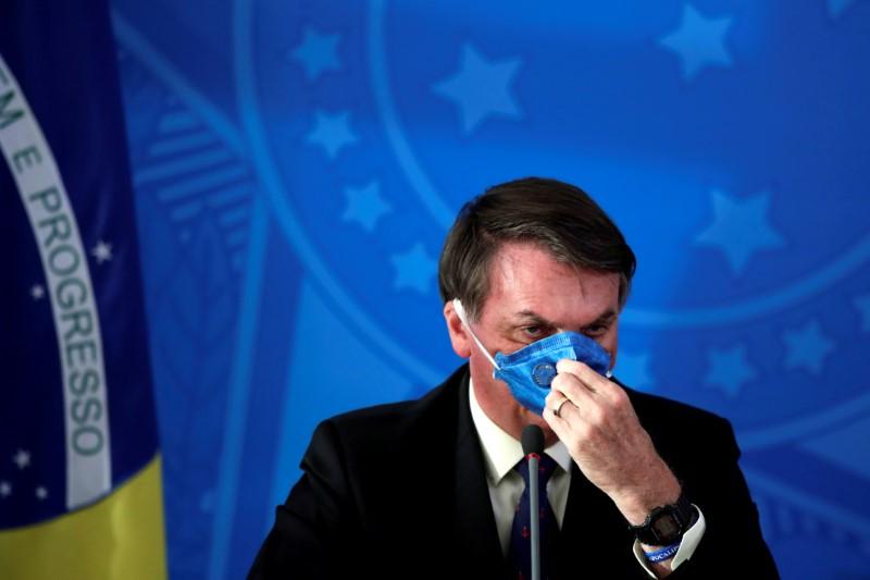 © Reuters. Brazil's President Jair Bolsonaro adjusts his protective face mask at a press statement during the coronavirus disease (COVID-19) outbreak in Brasilia