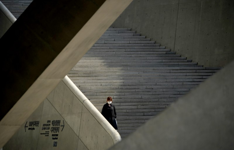 © Reuters. A woman wearing a protective face mask to prevent contracting the coronavirus disease (COVID-19) walks stairs in Seoul