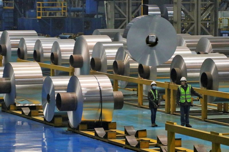 © Reuters. FILE PHOTO:  Employees work at the production line of aluminium rolls at a factory in Zouping