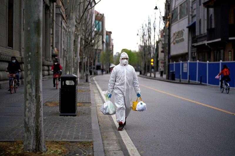 © Reuters. Man wearing a hazmat suit walks on a street in Wuhan