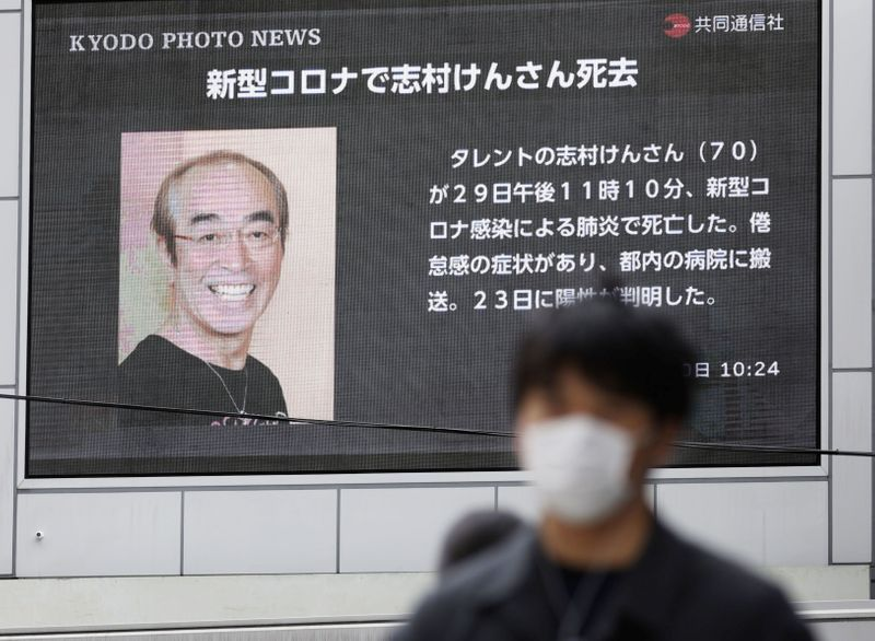 © Reuters. A man wearing a protective face mask walks past in front of a huge screen reporting death of Japanese comedian Ken Shimura in Osaka, western Japan