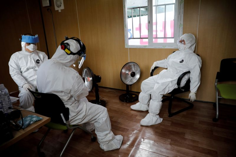 © Reuters. FILE PHOTO: Medical staff in protective gear take a break at a facility of a 'drive-thru' testing center for the novel coronavirus disease of COVID-19 in Yeungnam University Medical Center in Daegu