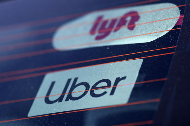 © Reuters. Uber and Lyft signs are seen on a car in Redondo Beach