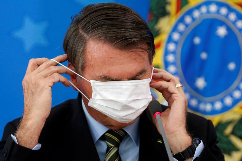 © Reuters. FILE PHOTO: Brazil's Jair Bolsonaro adjusts his protective face mask during a news conference to announce measures to curb the spread of the coronavirus disease (COVID-19) in Brasilia