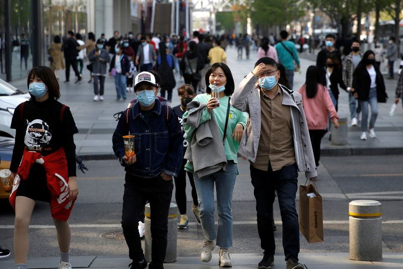 © Reuters. People wearing face masks are seen at a shopping area in Beijing