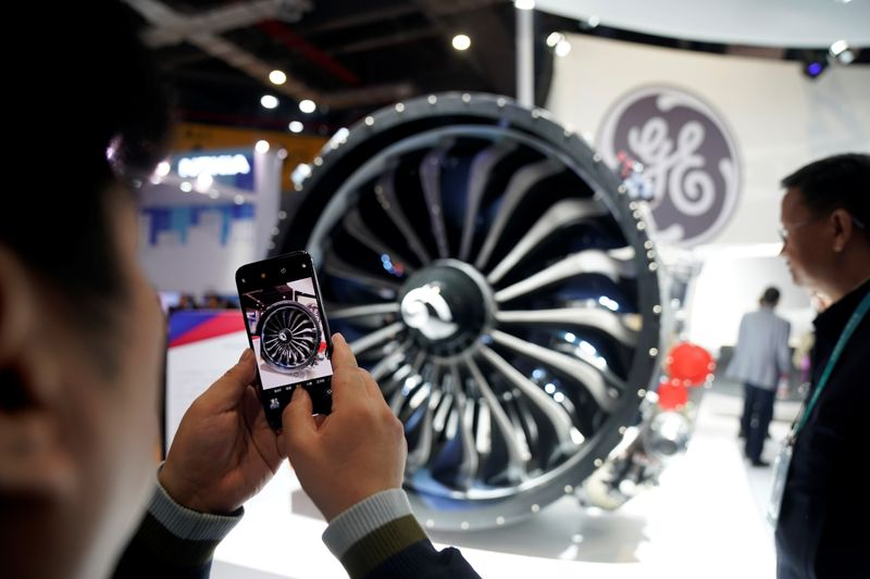 © Reuters. A man takes a picture of a General Electric (GE) engine during the China International Import Expo (CIIE), at the National Exhibition and Convention Center in Shanghai