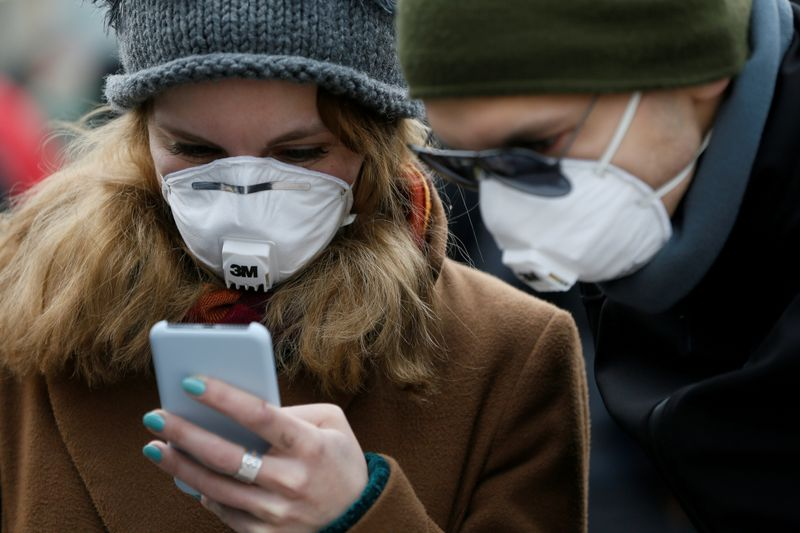 © Reuters. FILE PHOTO: People wearing protective face masks use a smartphone on a street in Kiev
