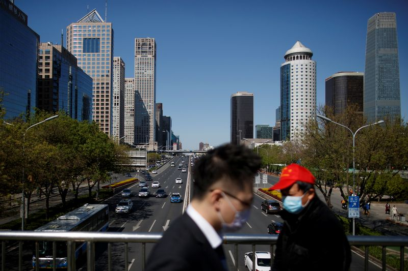 """© Reuters. People wearing protective masks cross a bridge in the Central Business District on a """"blue sky day"""