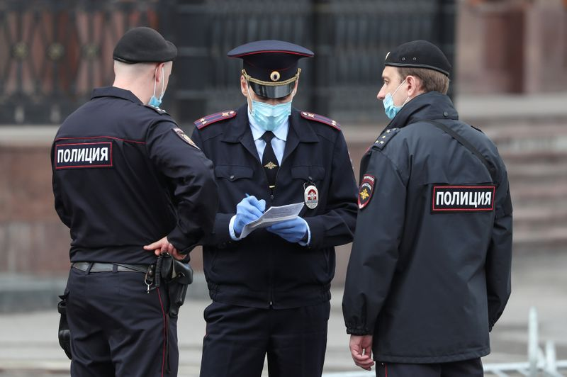 © Reuters. Police officers wearing protective face masks speak in a street amid the outbreak of the coronavirus disease in Moscow