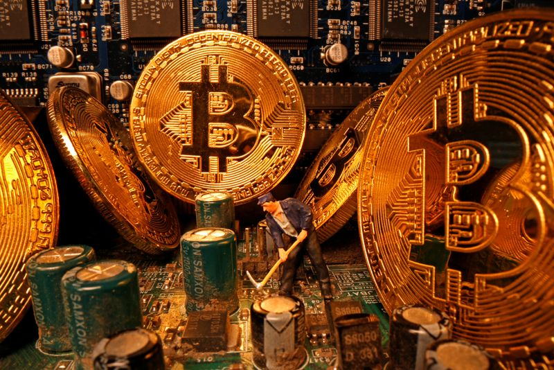 © Reuters. A small toy figure and representations of the virtual currency Bitcoin stand on a motherboard in this picture illustration