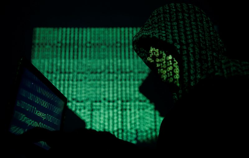 © Reuters. Hooded man holds a laptop computer as cyber code is projected on him in this illustration picture