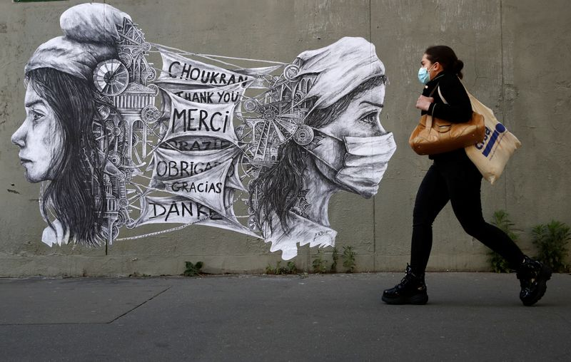© Reuters. A woman walks past a mural to thank the caregivers and the workers in Paris