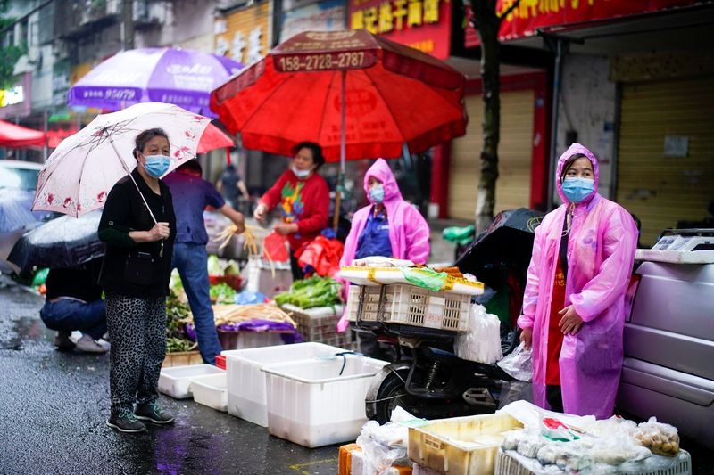 © Reuters. People wearing protective face masks are seen at a street market in Wuhan