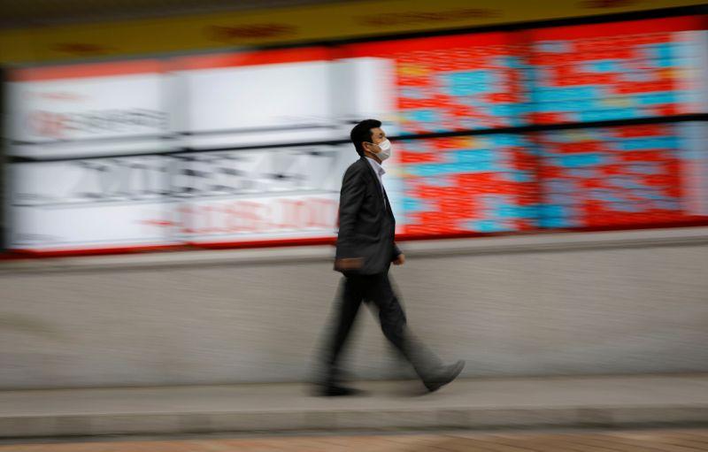 © Reuters. Pedestre com máscara de proteção caminha pelas ruas de Tóquio