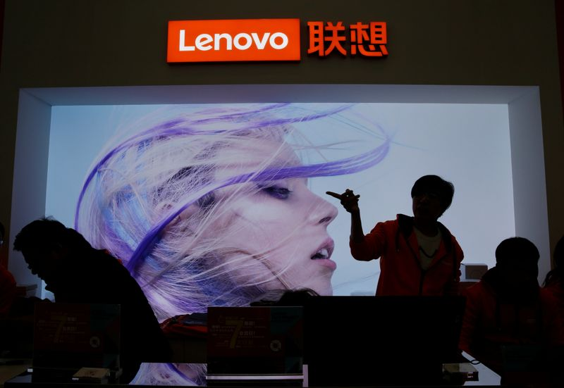 © Reuters. An employee gestures next to a Lenovo logo at Lenovo Tech World in Beijing