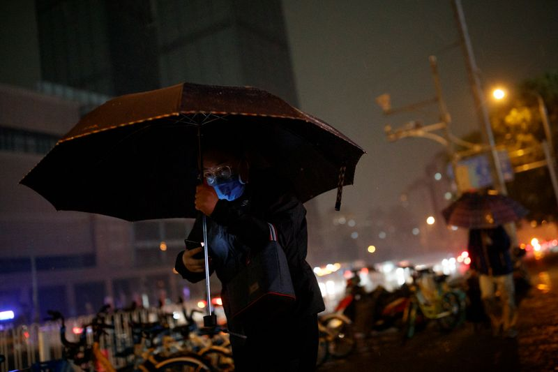 © Reuters. A man wearing a protective mask carries an umbrella as a sudden thunderstorm darkens the mid-afternoon sky in Beijing