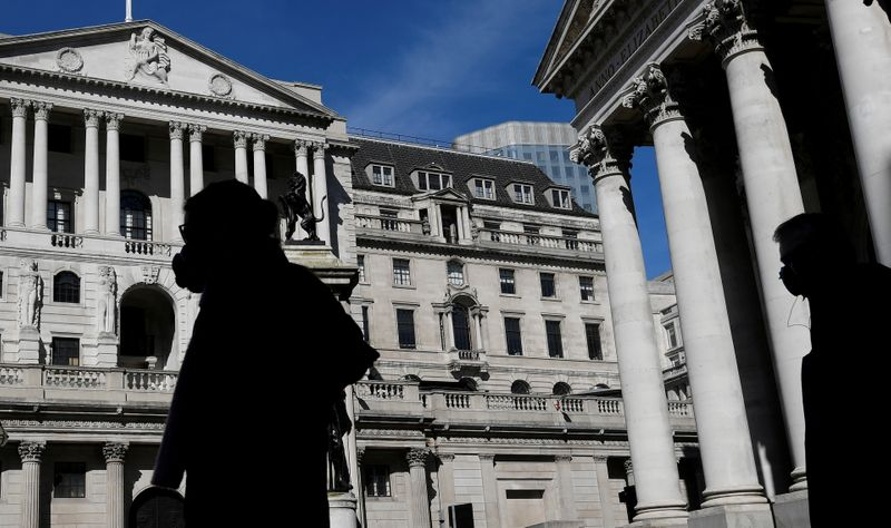 © Reuters. FILE PHOTO: People wearing masks walk past the Bank of England