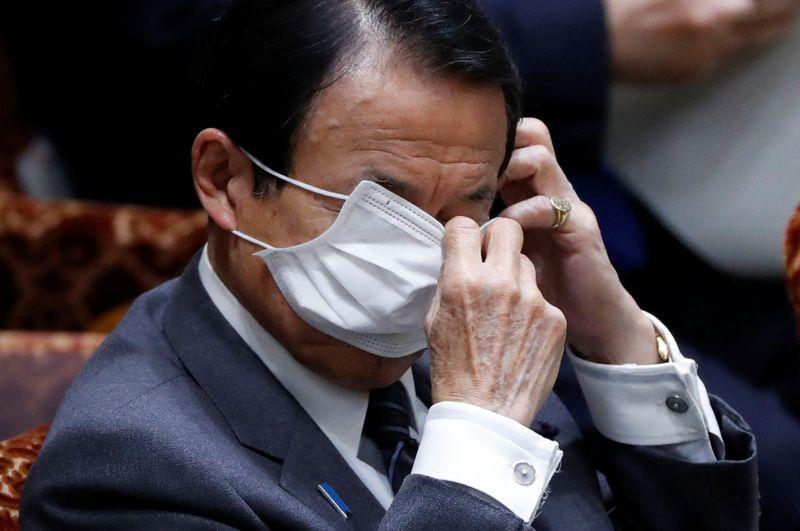 © Reuters. Ministro das Finanças japonês, Taro Aso, ajusta sua máscara durante sessão do Senado
