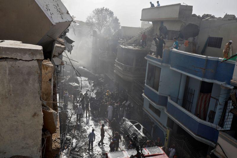 © Reuters. Agentes de resgate em local de queda de avião de passageiros em área residencial de Karachi, no Paquistão