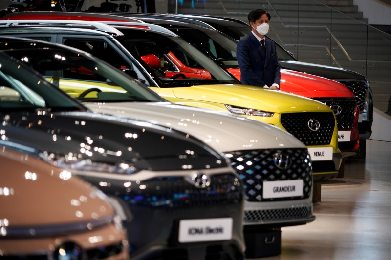 © Reuters. An employee wearing a mask to prevent contracting the coronavirus disease (COVID-19) waits for custormers next to a Hyundai Motor's vehicle at Hyundai Motor Studio in Goyang