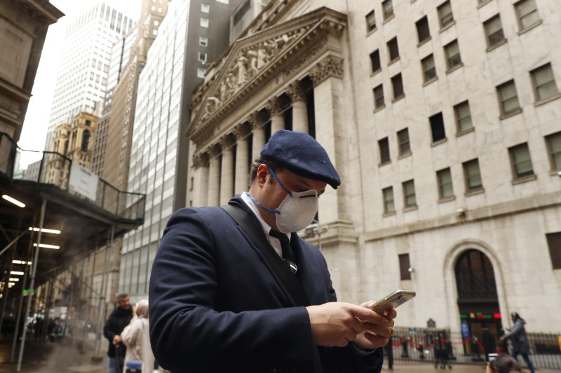 © Reuters. FILE PHOTO: FILE PHOTO: A man wears a protective mask as he walks on Wall Street during the coronavirus outbreak in New York