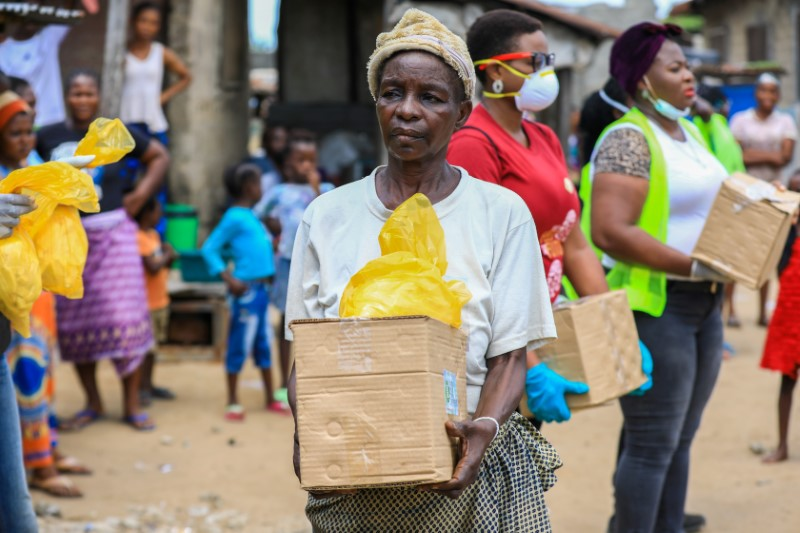 © Reuters. FILE PHOTO: An elderly woman is seen with a food parcel she received from volunteers at a relief distribution, during a lockdown by the authories in efforts to limit the spread of the coronavirus disease (COVID-19), in Lagos
