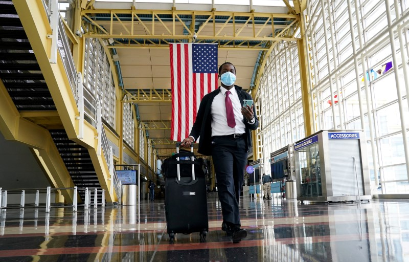 © Reuters. FILE PHOTO: Passenger walks through Reagan National airport as air travel continues to be minimal in Washington