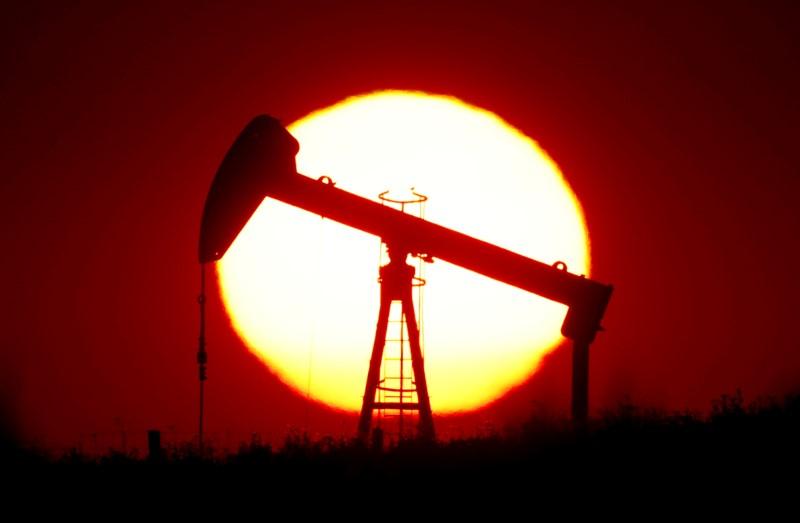 © Reuters. The sun sets behind a pump-jack outside Saint-Fiacre