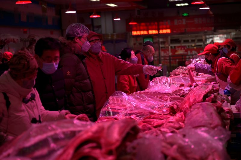 © Reuters. Customers wearing face masks buy pork meat at the Xinfadi wholesale market, as the country is hit by an outbreak of the novel coronavirus disease (COVID-19), in Beijing