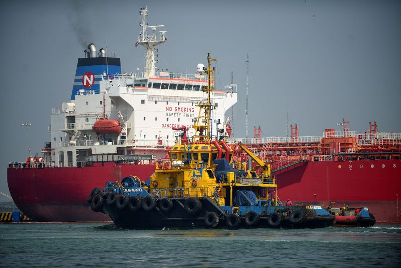 © Reuters. FILE PHOTO: A tug boat passes by an oil tanker docked at the port of Tuxpan