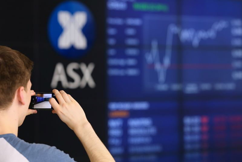 © Reuters. A visitor takes a photograph of a board displaying stock prices at the Australian Securities Exchange (ASX) in Sydney