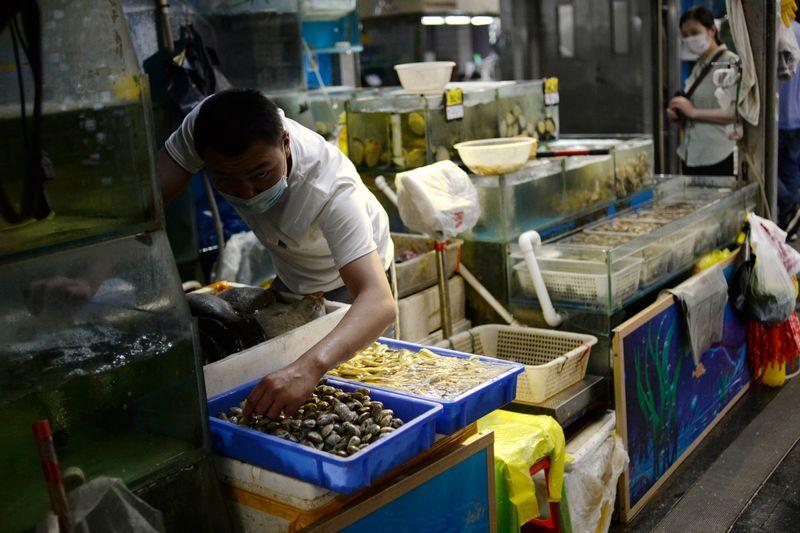 © Reuters. Los vendedores que usan una máscara facial están preparando mariscos en su puesto en el mercado mayorista de Yuegezhuang después de que ocurrieran nuevos casos de infecciones por la enfermedad por coronavirus (COVID-19) en Beijing