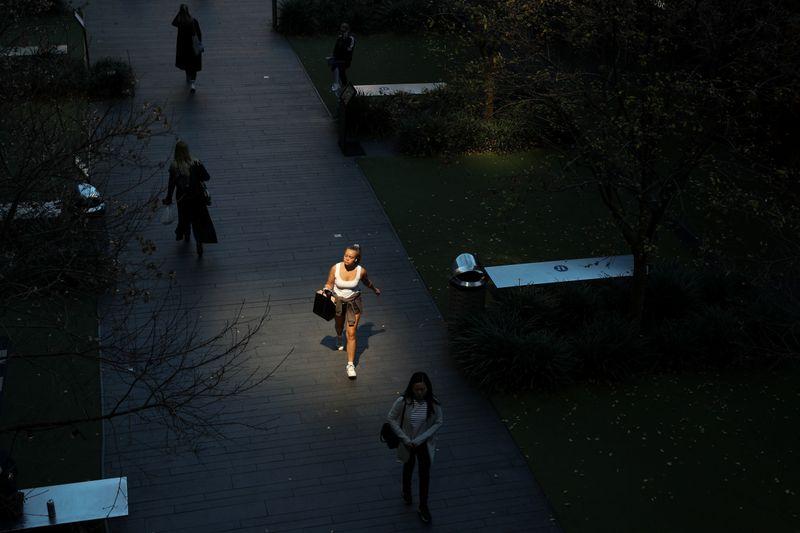 © Reuters. La gente camina hacia y desde una entrada a un centro comercial en el centro de la ciudad de Sydney