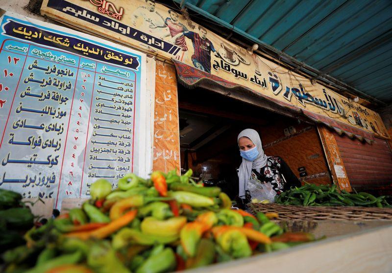 © Reuters. FOTO DE ARCHIVO: Una mujer compra verduras en una cafetería que se ha convertido en una verdulería de El Cairo.