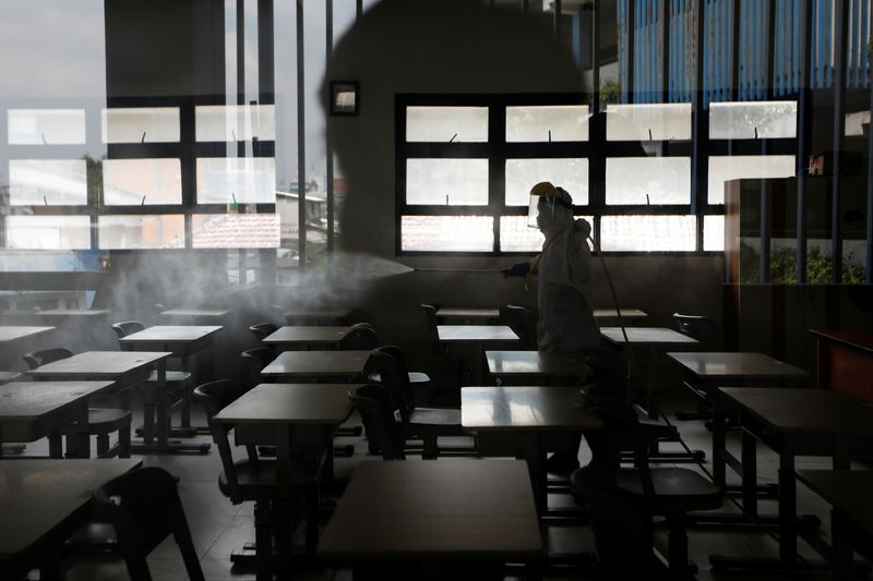 © Reuters. Personal de la Cruz Roja de Indonesia con desinfectantes en aerosol para equipo de protección en un aula de una escuela en Yakarta