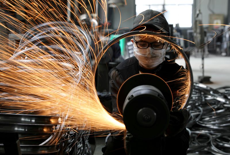 © Reuters. FILE PHOTO: Workers weld bicycle rims at a sports equipment factory in Hangzhou, Zhejiang