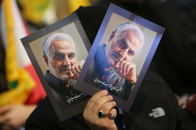 © Reuters. FILE PHOTO: A supporter of Lebanon's Hezbollah leader Sayyed Hassan Nasrallah carries pictures of the late Iran's Quds Force top commander Qassem Soleimani during a rally commemorating in Beirut's southern suburbs