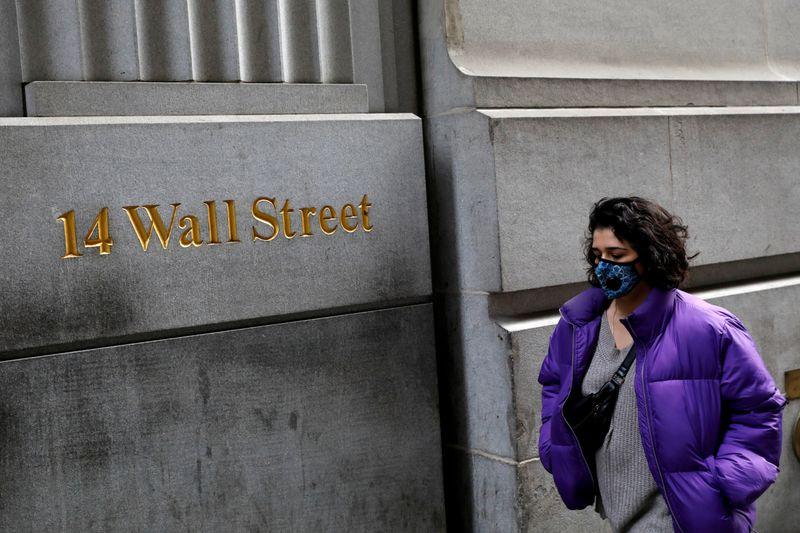 © Reuters. Una donna con indosso la mascherina cammina lungo Wall Street dopo che sono stati registrati nuovi casi di coronavirus a New York City
