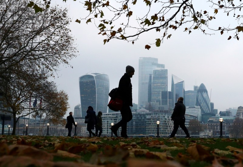 © Reuters. FILE PHOTO: People walk through autumnal leaves in front of the financial district in London