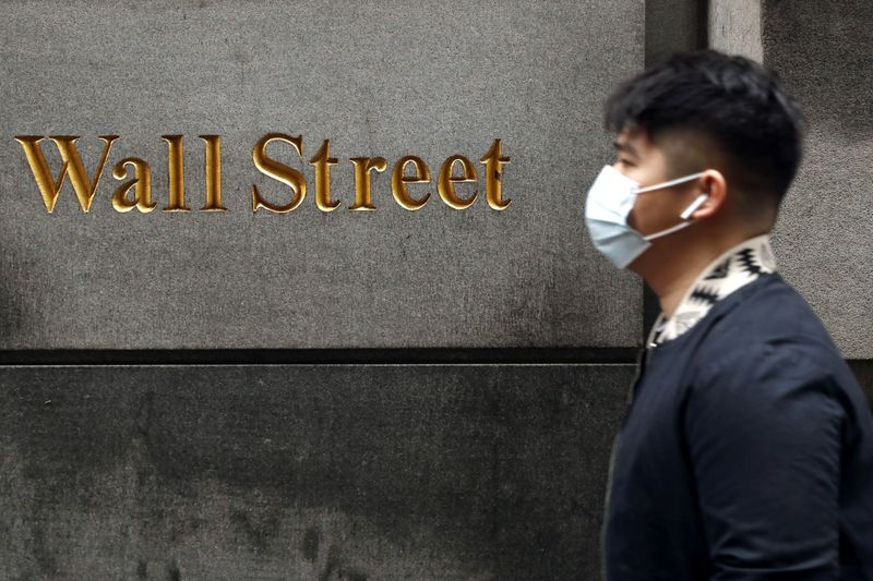 © Reuters. FILE PHOTO: A man wears a protective mask as he walks on Wall Street during the coronavirus outbreak in New York