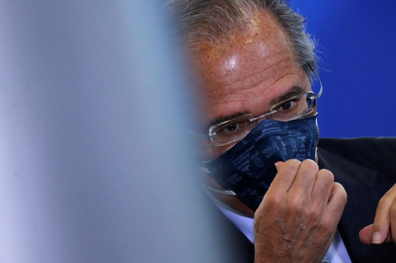 © Reuters. Brazil's Economy Minister Paulo Guedes adjusts his protective face mask before the inauguration ceremony of the new Communications Minister Fabio Faria (not pictured) at the Planalto Palace, in Brasilia