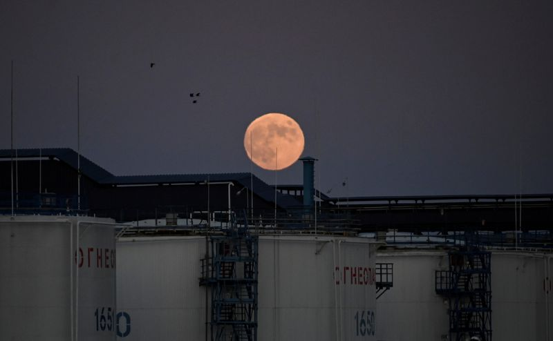 © Reuters. FILE PHOTO: The moon rises behind oil storage tanks in Omsk
