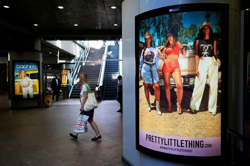 © Reuters. A shopper walks pass advertising billboards for Boohoo and for 'Pretty Little Things', a Boohoo brand, at Canary Wharf DLR station in central London