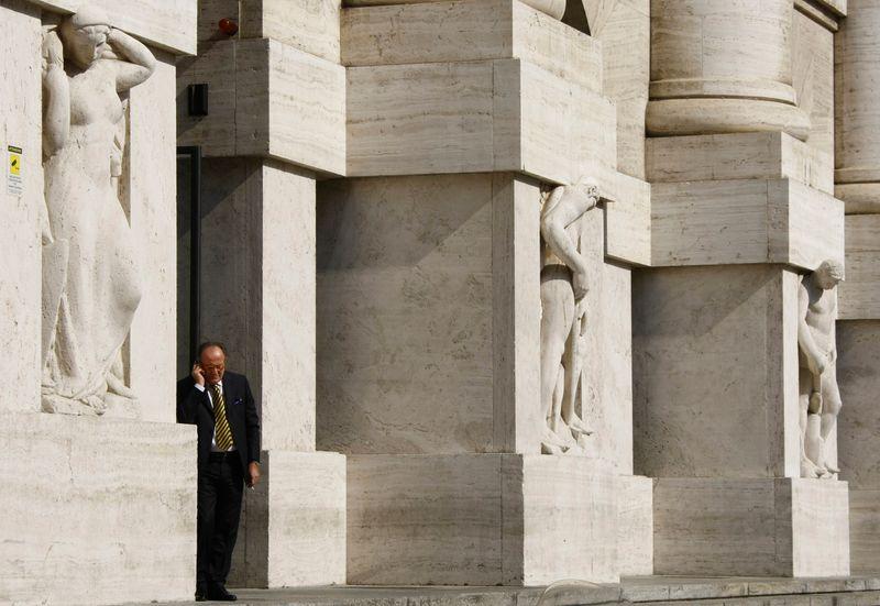 © Reuters. Un uomo in piedi fuori dalla sede della Borsa di Milano