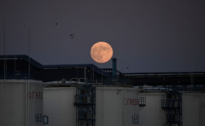 © Reuters. The moon rises behind oil storage tanks in Omsk