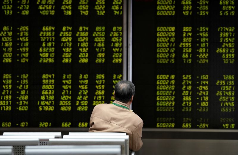 © Reuters. FILE PHOTO: An investor watches a board showing stock information at a brokerage office in Beijing
