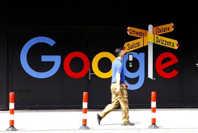 © Reuters. A man walks past a logo of Google in Zurich