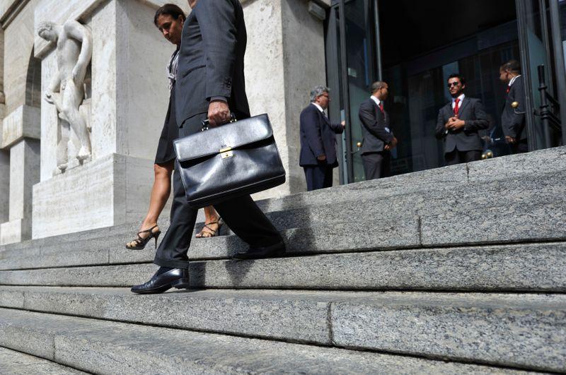 © Reuters. Diverse persone escono dalla Borsa di Milano