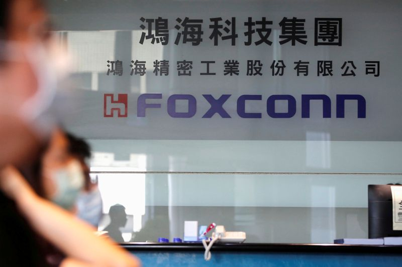 © Reuters. FILE PHOTO: People wear masks to protect themselves from coronavirus disease (COVID-19), while listening to the annual general meeting at the lobby of Foxconn's office in Taipei