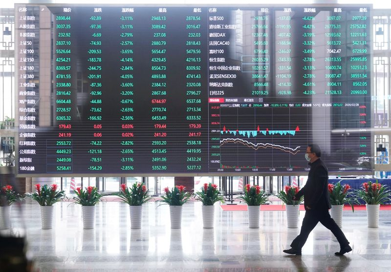 © Reuters. Man wearing a face mask is seen inside the Shanghai Stock Exchange building, as the country is hit by a novel coronavirus outbreak, at the Pudong financial district in Shanghai